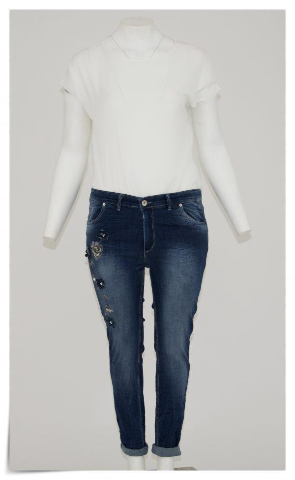 Jeans colore blu, 5 tasche bottone e cerniera, applicazione laterale di un ricamo a forma di fiore e perline