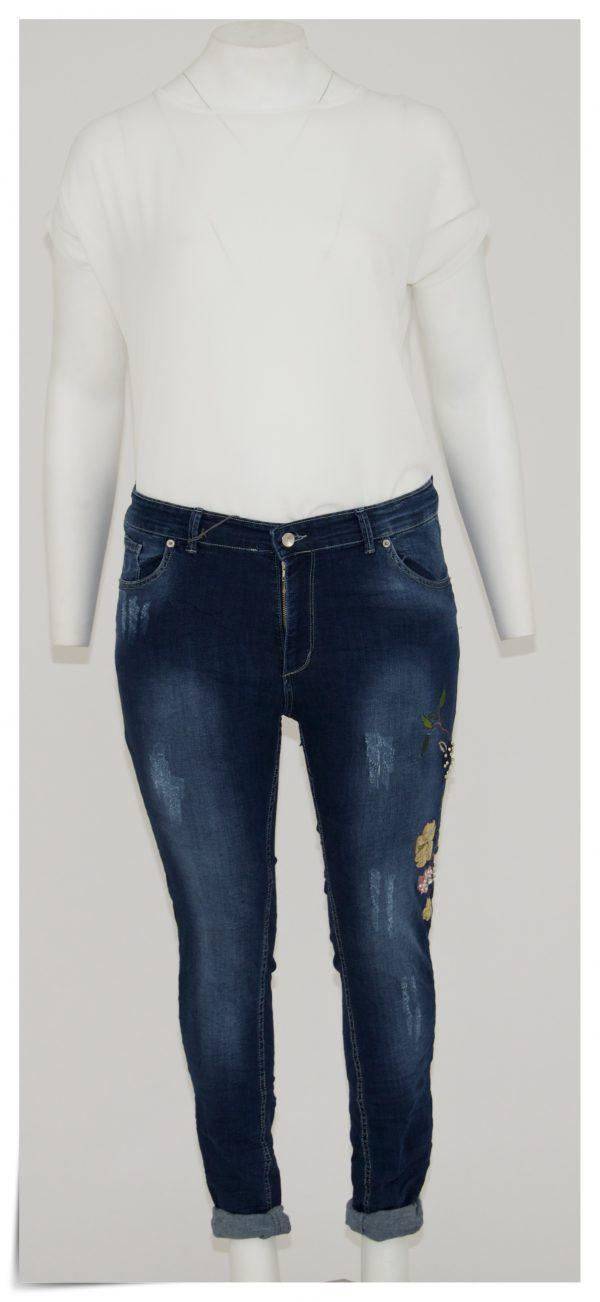 Jeans colore blu scuro, 5 tasche bottone e cerniera, graffiato con applicazione laterale di fiori con paillettes, perline e strass