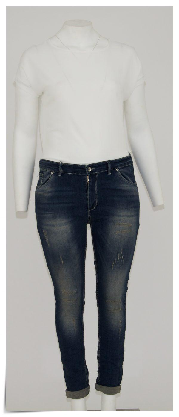 Jeans colore blu sfumato di beige, 5 tasche bottone e cerniera, graffiato nella parte davanti lungo tutta la gamba